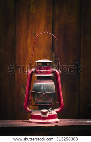 Still life of old hurricane lamp on wooden background - stock photo