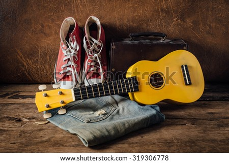 still life of pair of jeans and red sneakers,yellow ukulele on wooden floor with leather background