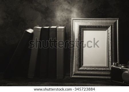 Still life of picture frame on table with vintage camera and diary book, Black and White image - stock photo
