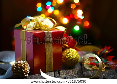 Still life of presents on wooden table with bokeh Christmas lights background - stock photo