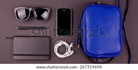 Still life of random objects of modern human. Handbag, cellphone, sunglasses, earphones, paper notepad, pen. Dark gray background. Aerial view. Concept.