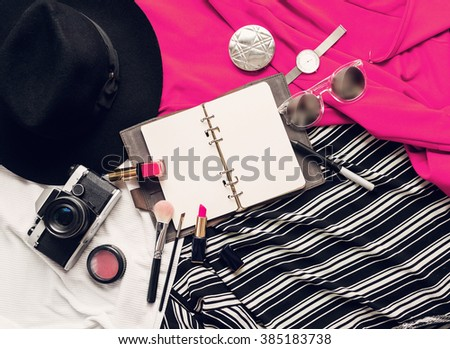 Still life of random objects. Outfit of stylish girl, woman, student or business lady .  Black hat, note book, sweatshirt, nail polish, lipstick, lip pencil, powder, glasses, watch, retro camera. - stock photo