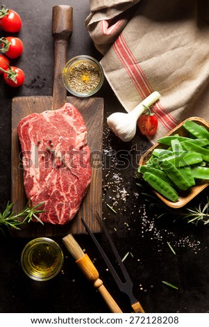 Still Life of Raw Ingredients for Preparing Dinner Meal - Raw Steak on Cutting Board, Snow Peas in Wooden Dish, Garlic Bulb and Various Herbs and Spices and Hand Towel - stock photo