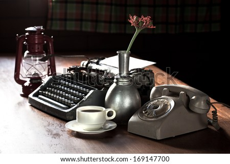 Still life of retro office, telephone, type writer and flower in silver vase place near old lamp on wooden table - stock photo