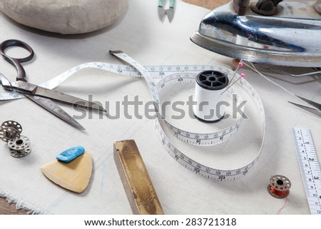Still life of set for needlework,Sewing kit. Scissors, bobbins with thread, measure tape, Iron and needles, Vintage style.  - stock photo