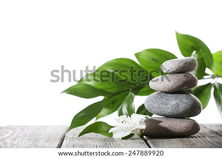 Still life of spa stones on wooden planks surface isolated on white - stock photo