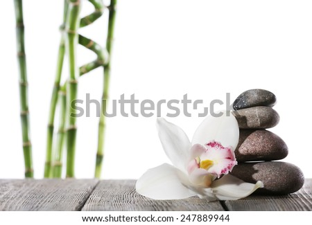 Still life of spa stones on wooden planks surface with bamboo sticks isolated on white - stock photo