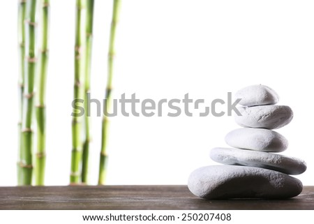 Still life of spa stones on wooden surface with bamboo sticks isolated on white - stock photo