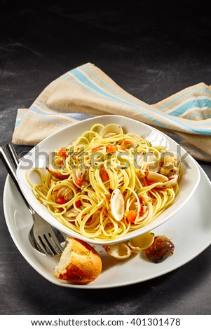Still Life of Spaghetti Pasta Noodles with Clams Served in White Bowl with Cutlery and Bread Roll, on Dark Table Surface with Cloth Napkin - stock photo