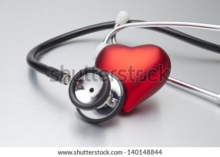 Still life of stethoscope and heart - stock photo