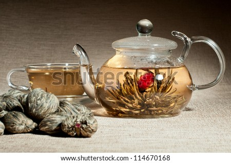 still life of the glass teapot and cup with green tea, on flax-fibre - stock photo