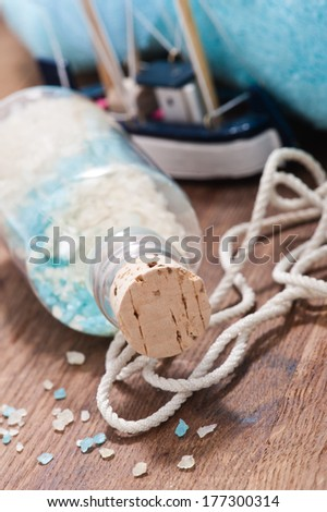 Still life of the mix of bath salts, nautical rope and toy ship - stock photo