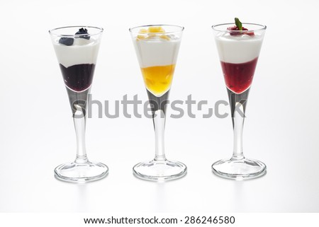 Still life of three cups with yogurt and three kinds of jam (blueberry, peach and strawberry) and decorative toppings of fruits - stock photo