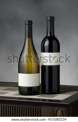 Still life of two wine bottle sitting on small wooden table with mottles gray background, blank labels - stock photo