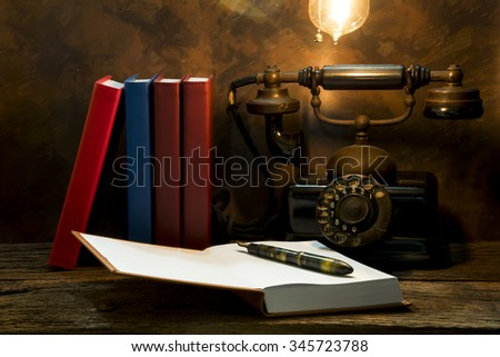 Still life of vintage telephone on table with diary book. - stock photo