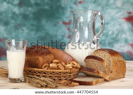 Still life of wheat spikelets, fresh bread, bagels and milk - stock photo