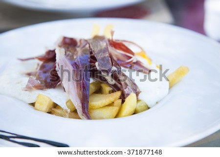 still life of white dish with typical Spain food named huevos rotos or broken eggs with potatoes french fries fried eggs and slices of iberico ham on table at cafe restaurant - stock photo