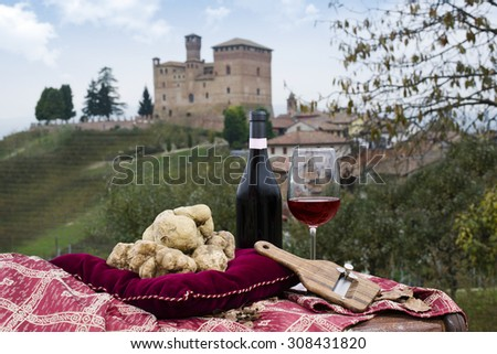 Still Life of White Truffles from Piedmont, truffles cuts and bottle with glass of red wine, with a view of the vineyards and the castle of Grinzane Cavour
