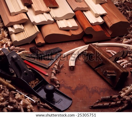 Still-life of wood moldings, wood shavings, and hand-tools. Block planes, carpenter's square, pencil. - stock photo