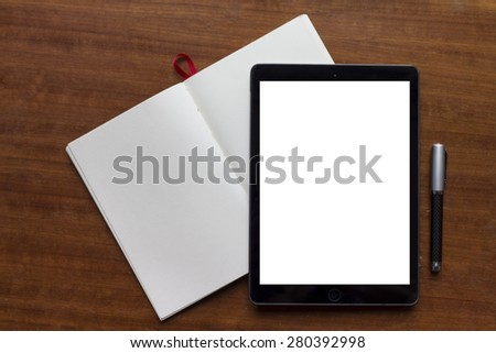 Still-life of work desk with tablet, notebook and pen.  White screen on device is easy to select and place your own website presentation page and show how amazing is looks.