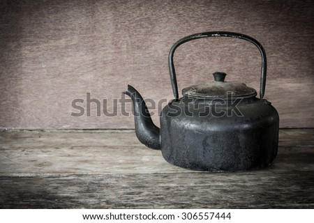 Still life old aluminium kettle on wood background. - stock photo