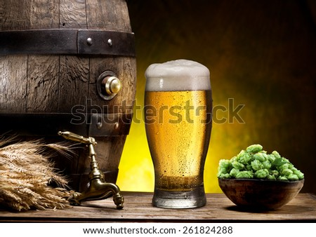 Still life: old wooden pin of beer, glass of beer and wheat on the table in the cellar. - stock photo