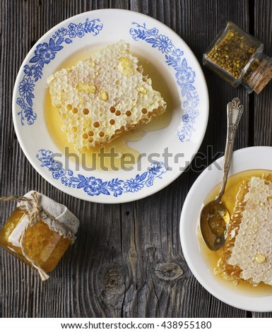 Still Life on a dark wooden background of pollen, honeycomb, fresh honey with a simple white ceramic bowl. The concept of a super food healthy organic food. - stock photo