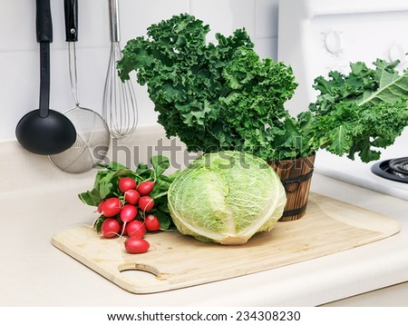 Still life on a kitchen table wooden board, ingredients for soup: green leaves of kale, radish, cabbage head, organic healthy food - stock photo