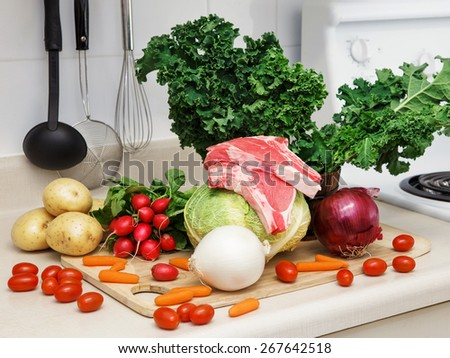 Still life on a kitchen table wooden board, ingredients for soup: green leaves of kale, red and white onion, reddish, white potato, cabbage head, tomato, carrot, raw meat, organic healthy food - stock photo