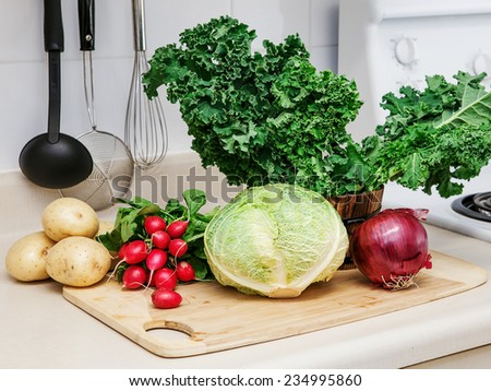 Still life on a kitchen table wooden board, ingredients for soup: green leaves of kale, red onion, radish, white yellow potato, cabbage head, organic healthy food - stock photo
