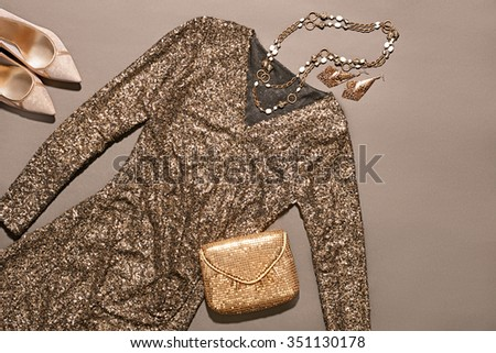 Still life Outfit  Top view. Fashion clothes stylish set, sequins dress and accessories. Glamor creative, trendy gold clutch, necklaces, earrings, luxury shoes heels.  Unusual evening party style - stock photo