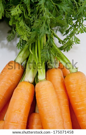 Still life over head close up detail of a bunch of healthy fresh and organic sweet carrots with growing leaves on a white background. Healthy diet foods and vegetables with vitamins.