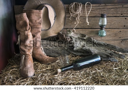 Still life painting photography with traditional leather boots and american west rodeo brown felt cowboy hat in vintage ranch barn background - stock photo