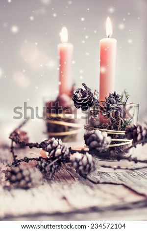 Still life photo of a Christmas candles burning bright with pine cones on rustic wooden background - stock photo