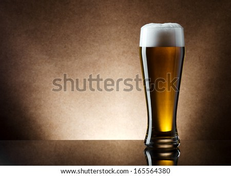 Still life photo of light lager beer in high glass. - stock photo