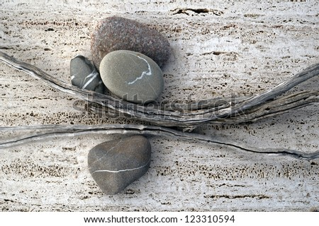 Still life photograph of weathered sticks and river stones.