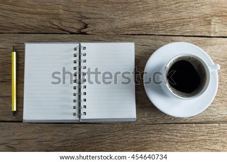 Still life photography, Black coffee with notebook,smartphone on wooden table. top view