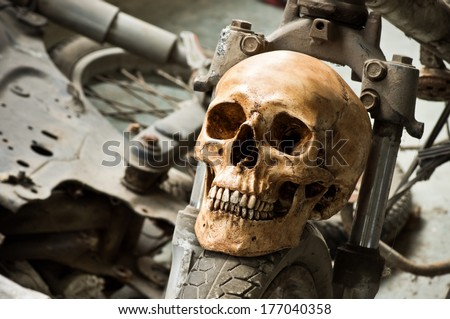 Still life photography, Human skull on front wheel of old motorcycle in junkyard concept - stock photo