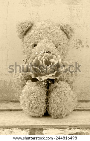 still life photography of cute bear doll holding rose bouquet in vintage style - stock photo