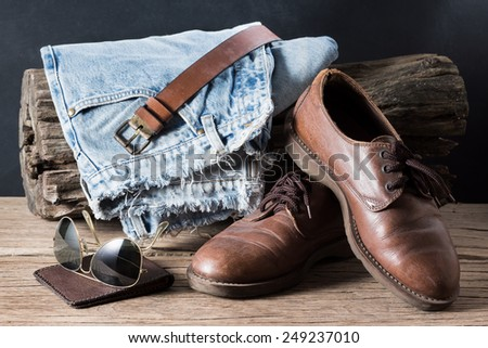still life photography : old jeans, leather shoe, wallet, sunglasses with tree stump on old wood in men casual concept