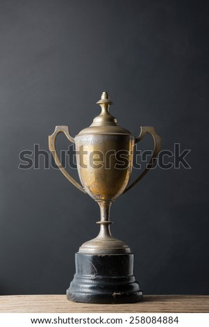 still life photography : old trophy on old wood with art dark background - stock photo
