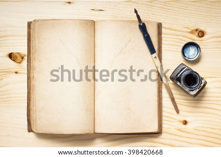 still life photography : quill pen with inkwell and opening old book on pine wood table