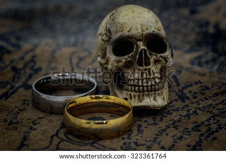 Still life photography rings and human skull - stock photo