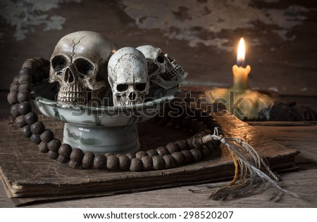 still life photography : skull and rosary in ceramic offering dish on old book in exorcist concept