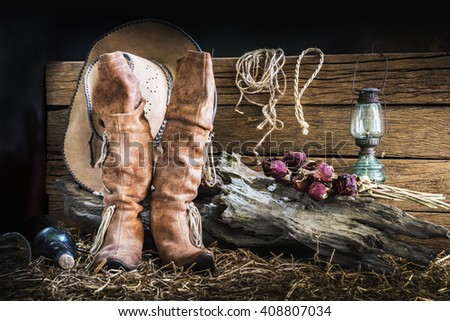 Still life photography with american west rodeo brown felt cowboy hat and traditional leather boots in vintage ranch barn background - stock photo
