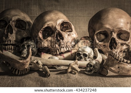 still life photography with closeup pile of skulls and animal bones on sackcloth background. Genocides concept, horror creepy halloween background - stock photo