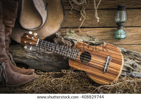 Still life photography with ukulele on american west rodeo brown cowboy hat and traditional leather boots in retro barn background