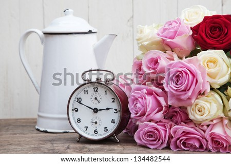 still life picture of a rose bouquet an old alarm clock and an old coffee can