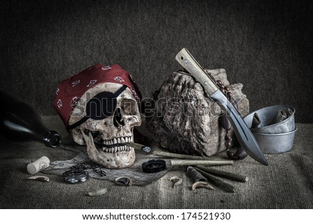 Still life, pirate skull with cigar, compass on ancient map, knife and pocket watch on the floor - stock photo