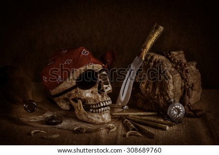 Still life, pirate skull with cigar in the mouth, compass on ancient map, knife and pocket watch hang on the log - stock photo